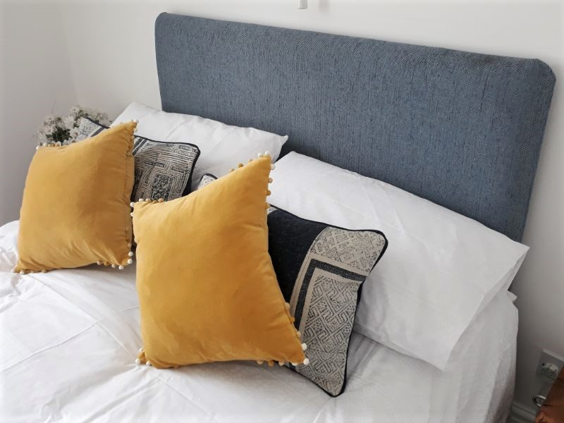 Simple headboard and cushions for a bedroom in a holiday cottage.