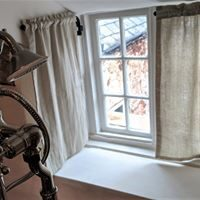White linen bathroom curtains fitted on portiere rods